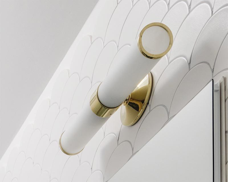 A simple white tube sconce with gold accents is mounted above the mirror, draws the eye upwards, and creates a soft glow for the bathroom. #BathroomLighting #BathroomDesign