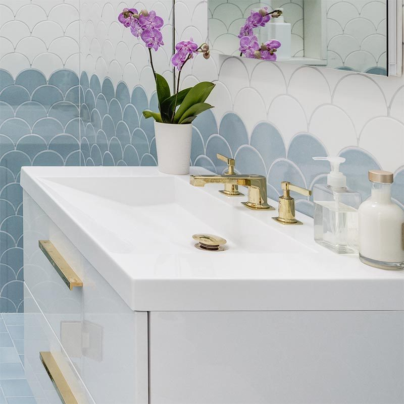 This modern bathroom is furnished with white vanity that has clean lines forming a rectangular shape, a built-in sloped sink, gold hardware in the form of the faucet, taps, drain, and drawer pulls.  #ModernBathroom #WhiteBathroomVanity #ModernVanity #BuiltInSink #GoldBathroomAccents