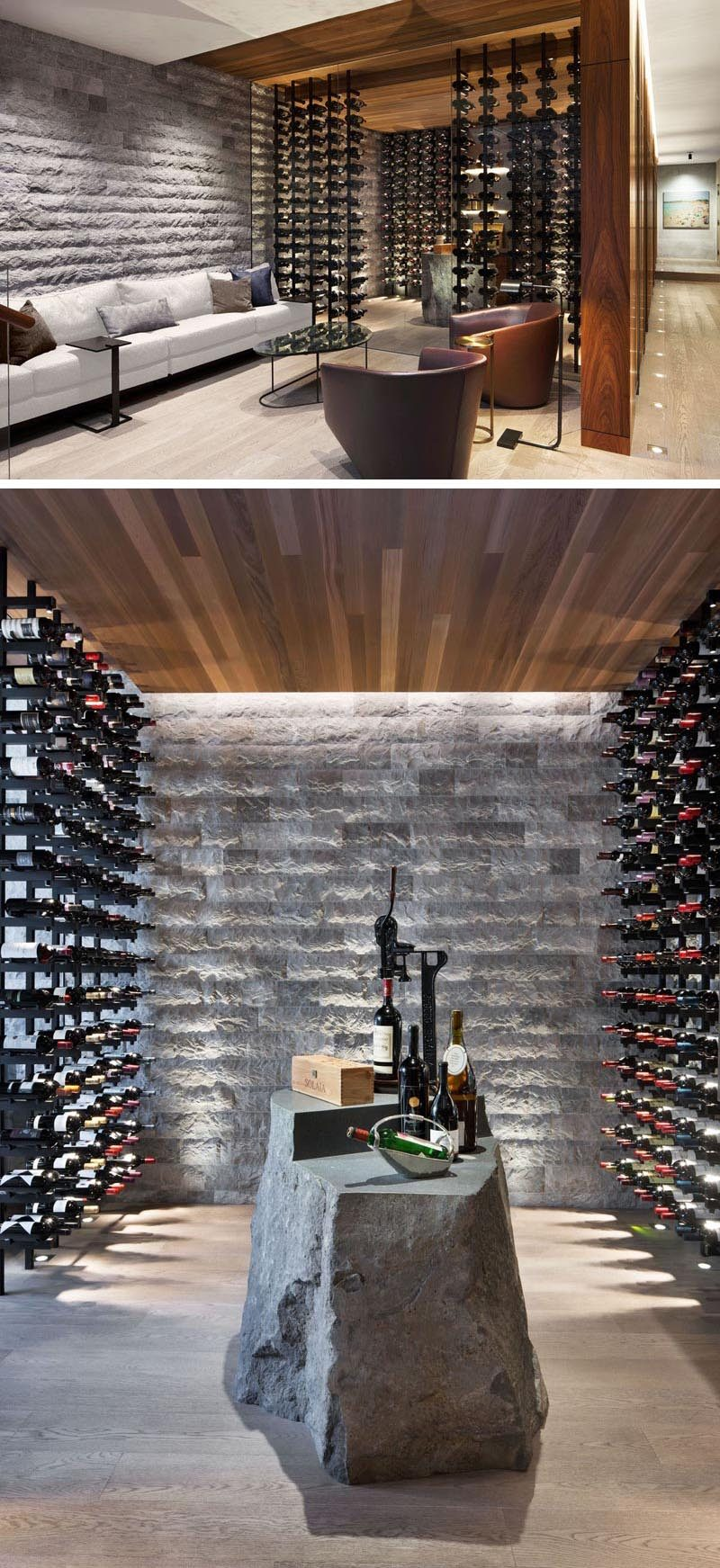 This modern wine cellar has glass walls, plenty of bottle storage, and a stone element that's been designed to be used as a table. #WineCellar #WineRoom #WineStorage