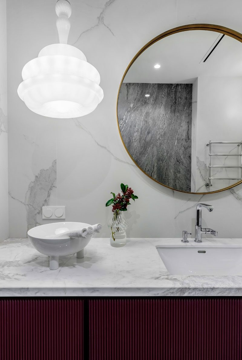 In this modern bathroom, grey marble covers the wall and vanity, while a Novecento suspension lamp from Vistosi hangs beside a circular mirror. #ModernBathroom #BathroomDesign #GreyBathroom
