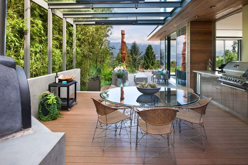 This modern outdoor dining area has a kitchen, wood burning oven, and bbq. #OutdoorDining #BBQ