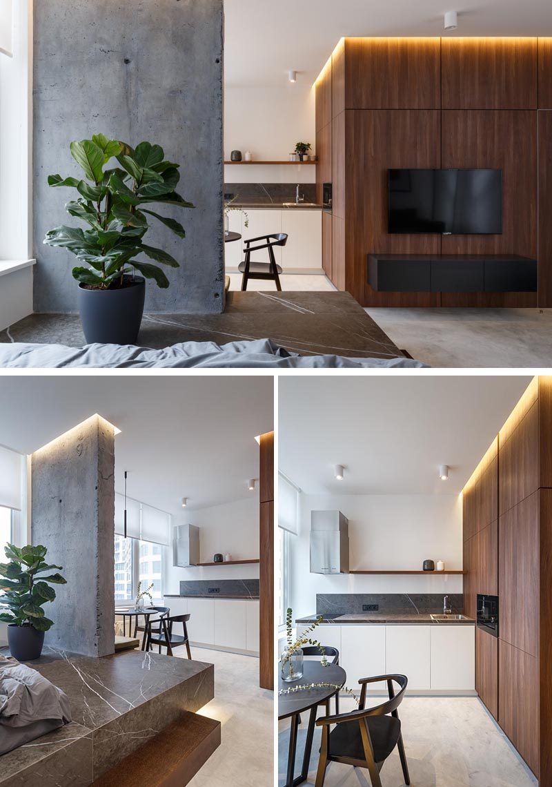 In this small apartment, the wood accent wall in the living room wraps around into the kitchen and dining area. The kitchen features minimalist white cabinets, built-in appliances, a grey countertop, and a simple floating wood shelf. #SmallApartment #WoodAccentWall #SmallKitchen
