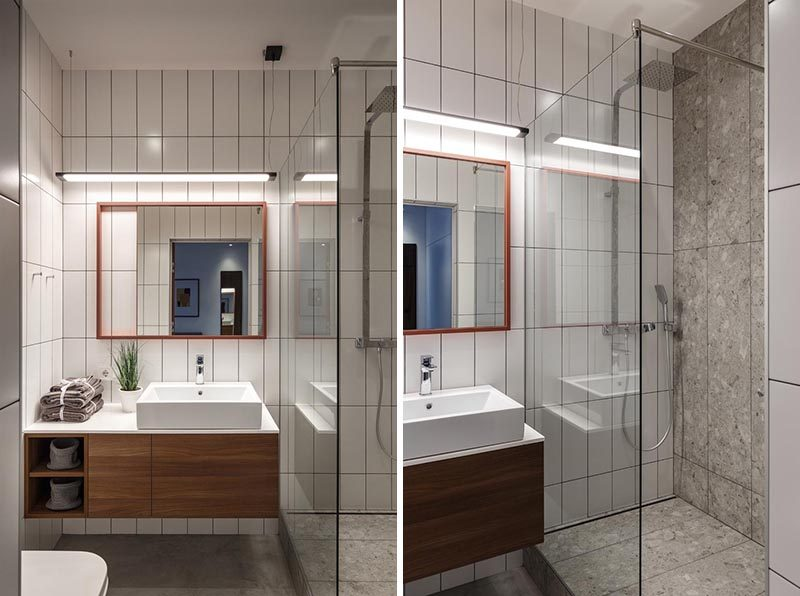 In this small bathroom, floor-to-ceiling rectangular tiles in a vertical arrangement cover the walls, while a wood vanity with a white countertop fits neatly beside the shower, that's separated by a glass screen. #SmallBathroom #WhiteTiles #BathroomDesign