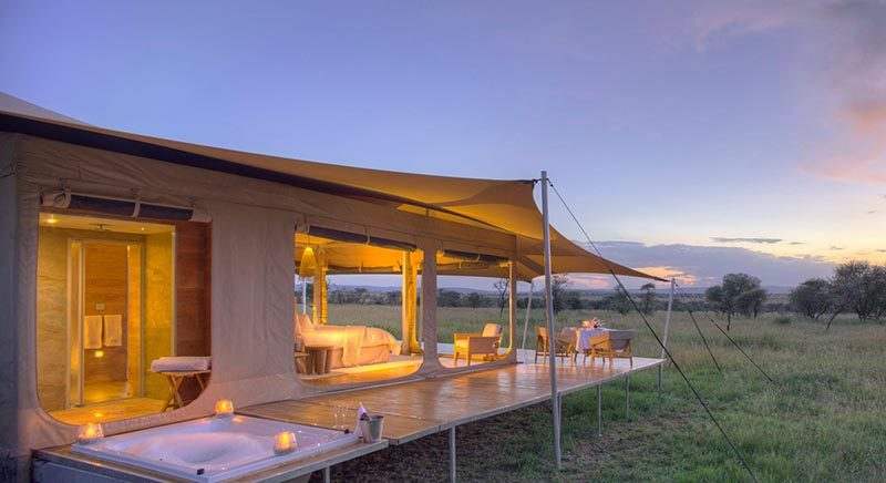 Raised up on a platform with wheels, this safari tent has an en-suite bathroom behind the sleeping area includes a flushing toilet, vanity basin and shower. The wrap around deck also features a sunken bath tub. #Serengeti #SafariCamp #SafariTent