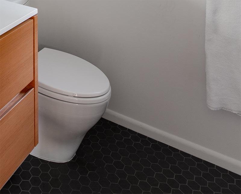 Dark grey hexagonal floor tiles have been used to contrast the wood vanity and white walls in this modern bathroom. #HexagonalFloorTiles #GreyTiles #HexagonalTiles