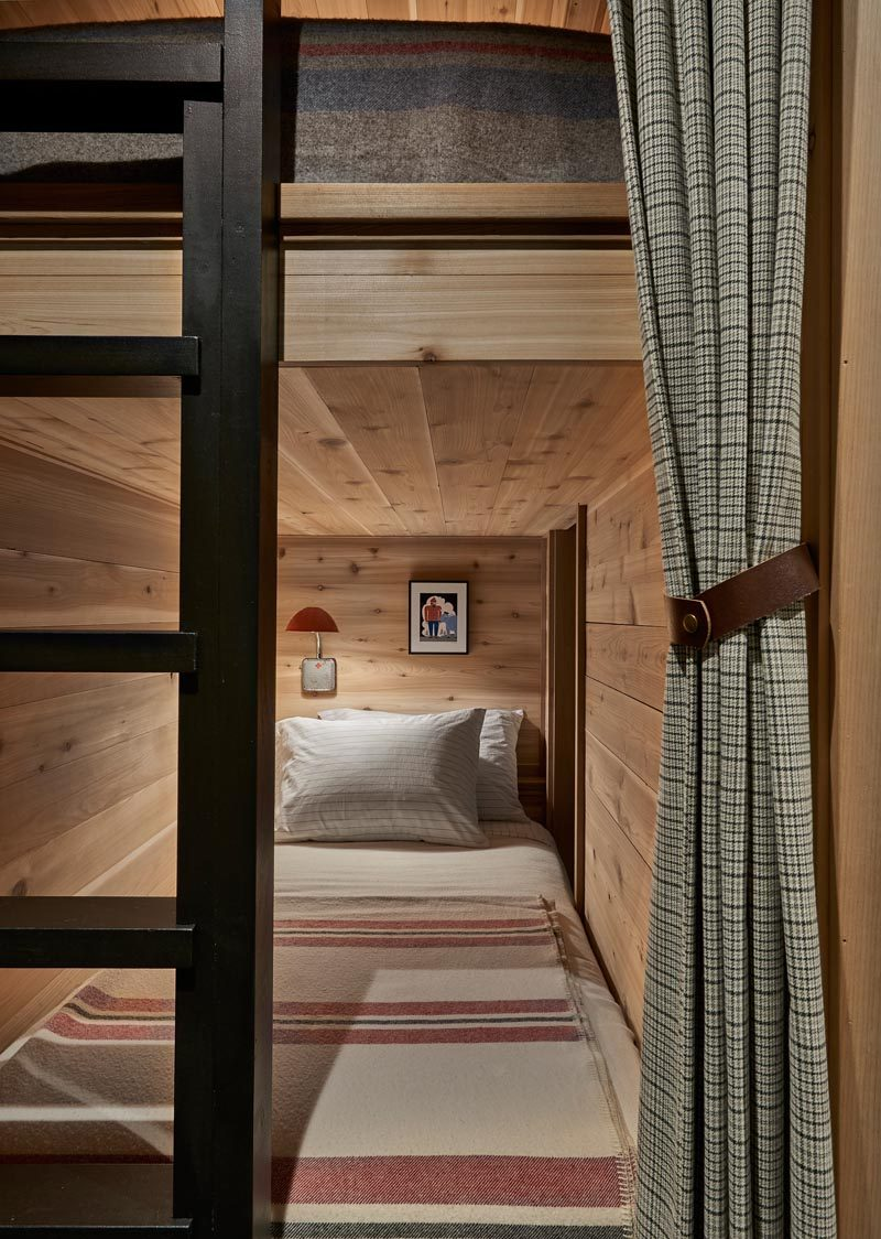 This modern house also has a room that houses two pairs of bunk beds. Curtains provide privacy, while black ladders allows for ease of access., and lamps create a source of light. #BunkBeds #Bunks