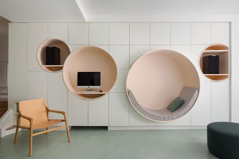 This modern living room has a wall of minimalist white cabinetry with multiple circular niches designed with different uses in mind. The largest circle has been defined as a reading nook, with an upholstered cushion that lines the bottom half of the shape, while the others have shelving for a computer and speakers. #ReadingNook #SeatingNiche #InteriorDesign