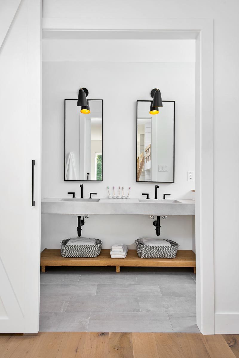 This modern bathroom features custom concrete counter tops by Chicago Concrete, concrete porcelain tile from Porcelanosa and Virginia Tile, wrought iron plumbing fixtures and accessories, and custom mirrors #ModernBathroom #ConcreteCounter #BathroomDesign