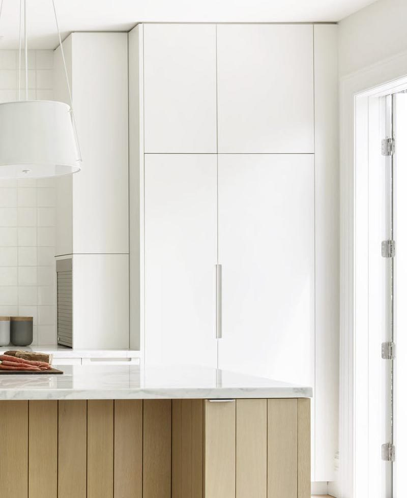 In this modern kitchen, minimalist white cabinets travel from the floor to the ceiling, while a small appliance garage is tucked away into one of the side panels. #WhiteCabinets #ModernKitchen #KitchenDesign #ApplianceGarage