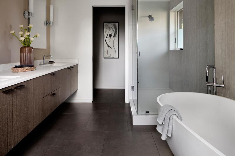 In this modern master bathroom, dark tiles contrast the light colored walls, the freestanding bathtub, and the white counters of the floating wood vanity. #ModernMasterBathroom #ModernBathroom #BathroomDesign