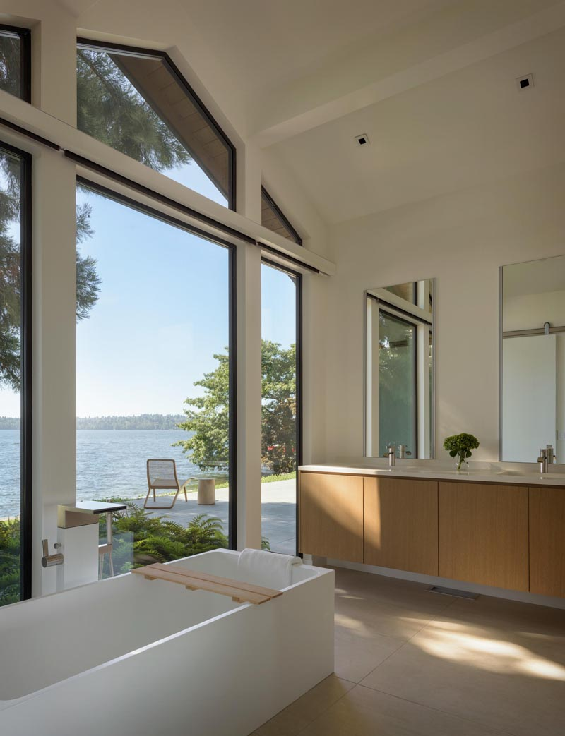 In this modern master bathroom, the main focus is the view of the lake through the floor to ceiling windows that follow the line of the roof. #Windows #ModernBathroom #BathroomDesign
