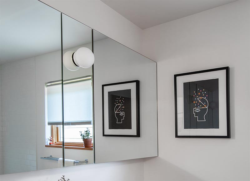 A custom mirror-front medicine cabinet was designed for the bathroom, while a new Fir-framed window replaced the old window. #BathroomRemodel #ModernBathroom #BathroomMirror