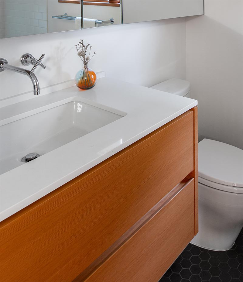 """Bathroom Remodel -The dated cream colored vanity with matching tile countertop was replaced by a floating wood vanity with porcelain undermount sink and a 3/4"""" Caesarstone countertop. #BathroomVanity #BathroomRemodel #ModernBathroom"""