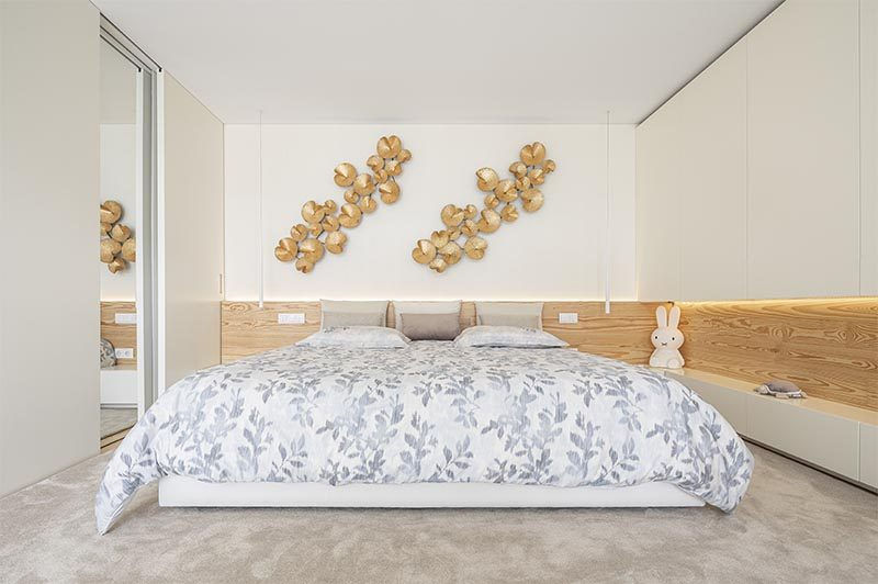 The wood accent adds a natural element to this modern bedroom and creates a headboard for the bed, while between the cabinets to the right of the bed, has hidden lighting, adding a soft glow to the room and highlighting the displayed objects on the shelf. #BedroomDesign #ModernBedroom #WoodAccent, #Lighting