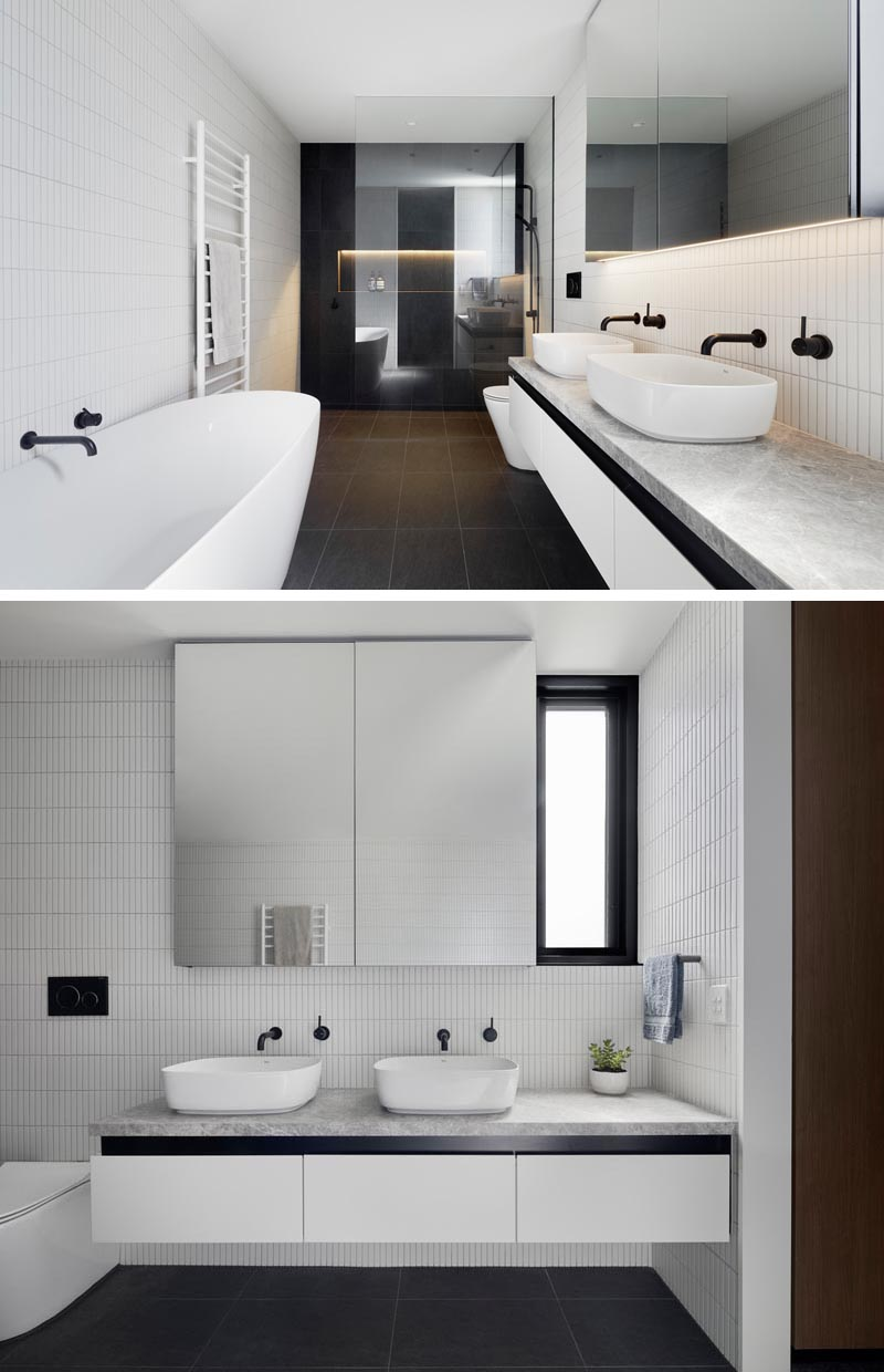In the shower of this modern bathroom, black wall tiles are brightened by a shower niche with hidden lighting. A glass shower screen allows light to travel throughout the room. Contrasting the black tiles are the white tiles on the walls and other white accents like the bathtub, towel rack, vanity, and sinks. #ModernBathroom #BlackAndWhiteBathroom #BathroomDesign #BlackTiles #ShowerNiche