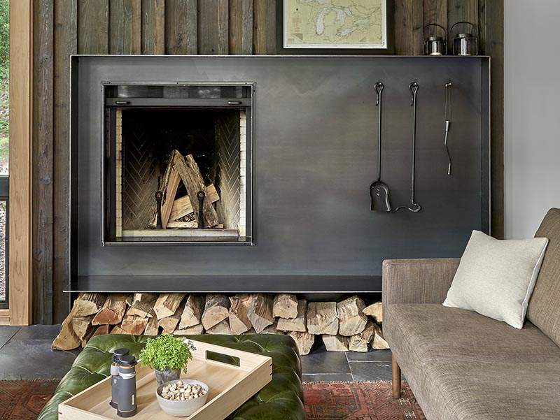 A modern living room in a weekend retreat features a hand-worked blackened steel fireplace surround. #Fireplace #BlackFireplaceSurround #SteelFireplace