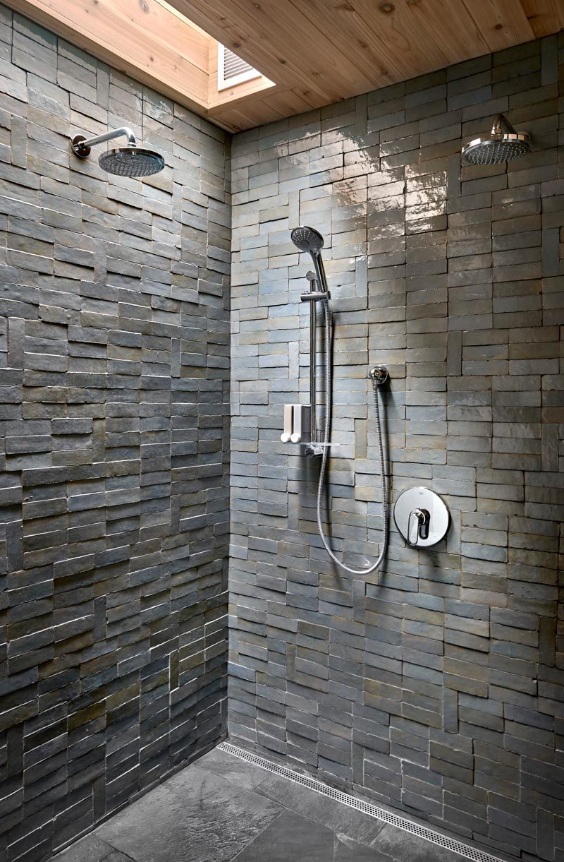 This modern bathroom has a shower with a skylight that highlights the texture and coloring of the handmade tiles that clad its walls. #Shower #ShowerDeisgn #BathroomDesign