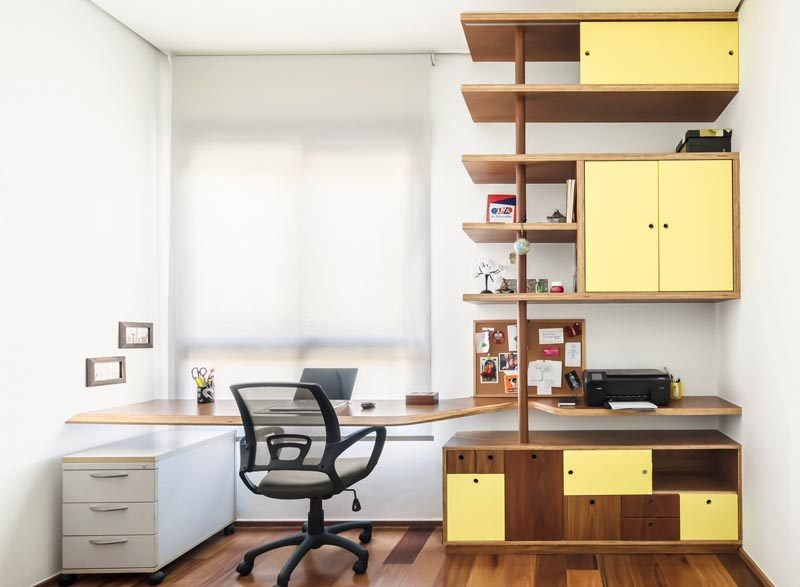 In this modern home office, there's a custom-designed desk that fills the width of the wall, and a wood shelving unit that adds a soft pop of color with yellow doors. #HomeOffice #ModernDesk #Shelving