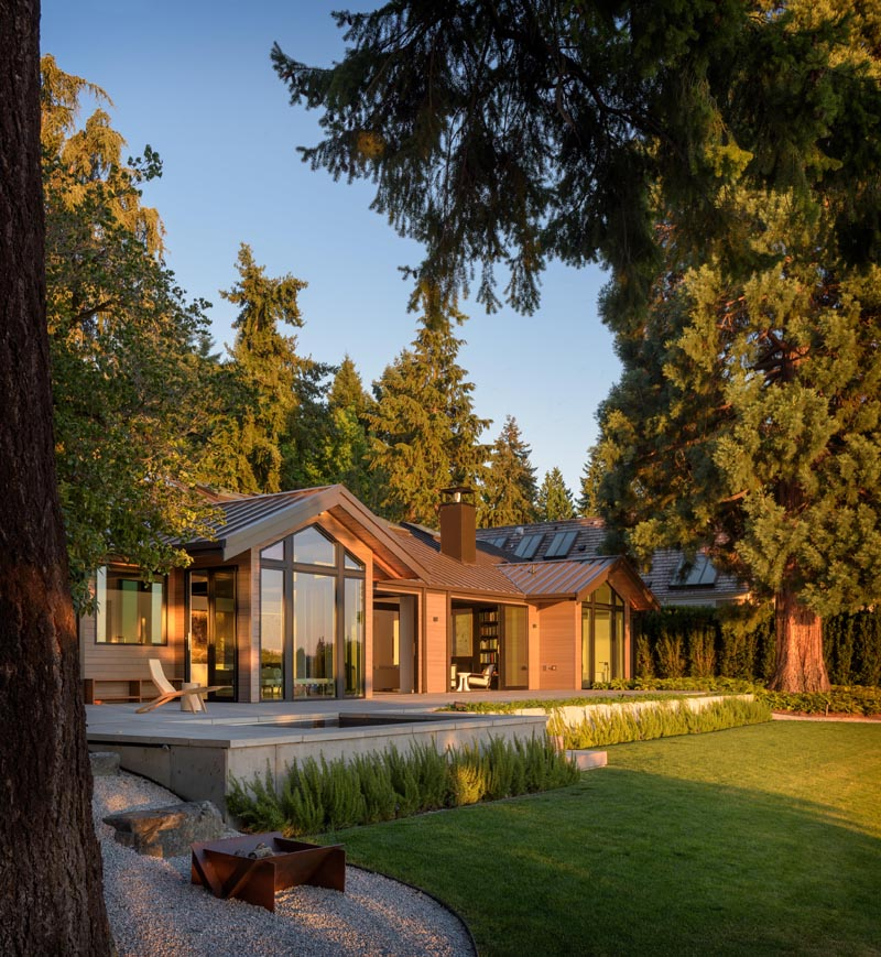 Large operable doors and window walls helped optimize natural light throughout the home and provided views to nearby Lake Washington. The doors open to a deck that steps down to a grassy yard with access to the water. #Architecture #Landscaping #Yard