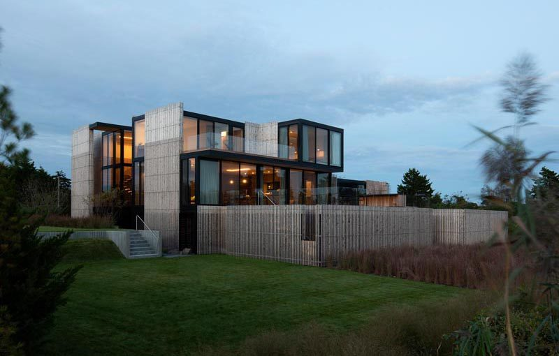Bates Masi + Architects has completed a new and modern house in Sagaponack, New York, that has an elevated design due to the it being located on a flood-prone site. #ModernHouse #ModernArchitecture #HouseDesign #WoodFacade