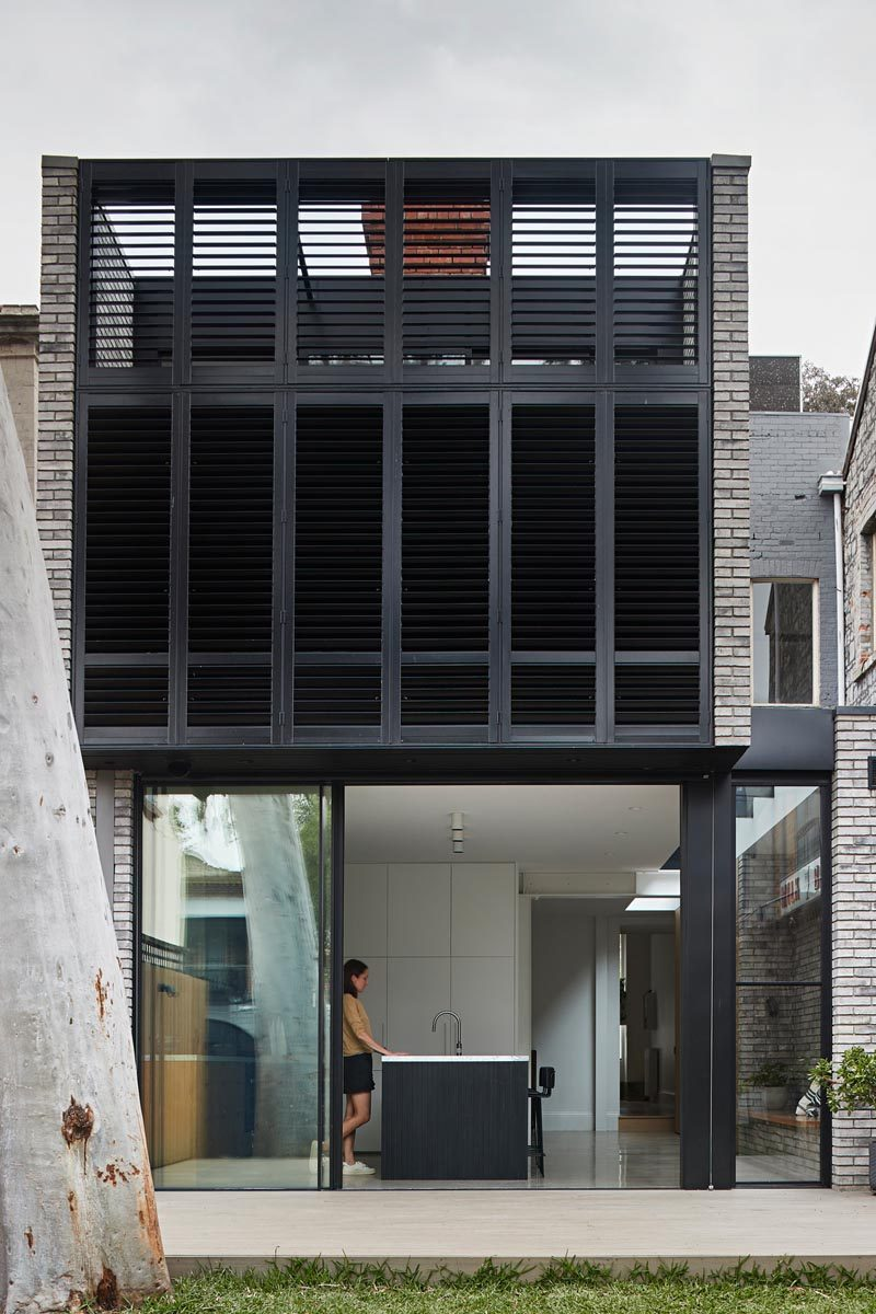 A black-framed sliding door opens this modern kitchen to the backyard, where a large gum tree provides shade and is the focus of the outdoor space. From this view, you can see the black louvers that hide a private balcony off the master bedroom. #ModernArchitecture #Louvers #ModernHouse