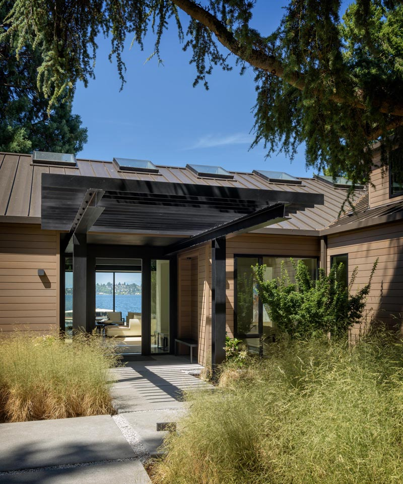 "This modern house had a former rustic ""lodge style"" exterior was updated to a refined language of taut wood planes with a crisp metal roof and windows. #ModernHouse #WoodSiding #Architecture #Entryway #Landscaping"