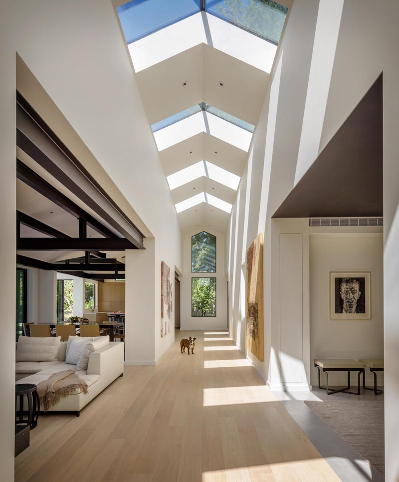 This modern home is organized around a central gallery spine with skylights that draw abundant natural light into the core of the house and surrounding rooms. #Skylights #Hallway #ModernHouse #Architecture