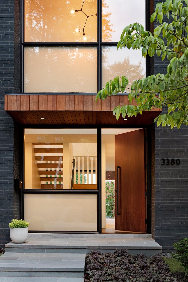 A wood front door welcomes visitors to this modern house and opens to a small light-filled foyer. #ModernFrontDoor #Windows