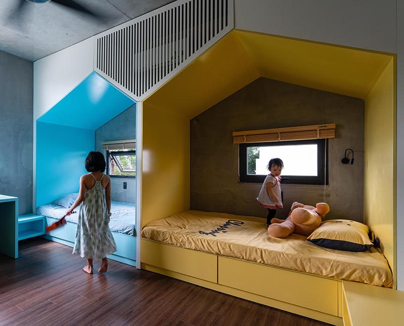 This modern bedroom, which features wood floors, has two mini 'houses' that define the separate sleeping areas for the children. The houses, each with their own window, create a little nook for each child, giving them their own space when needed, while a combined shelf and desk is color matched to the bed. #KidsBedroom #BedroomDesign #SharedKidsBedroom #ChildrensBedroom #ModernKidsBedroom