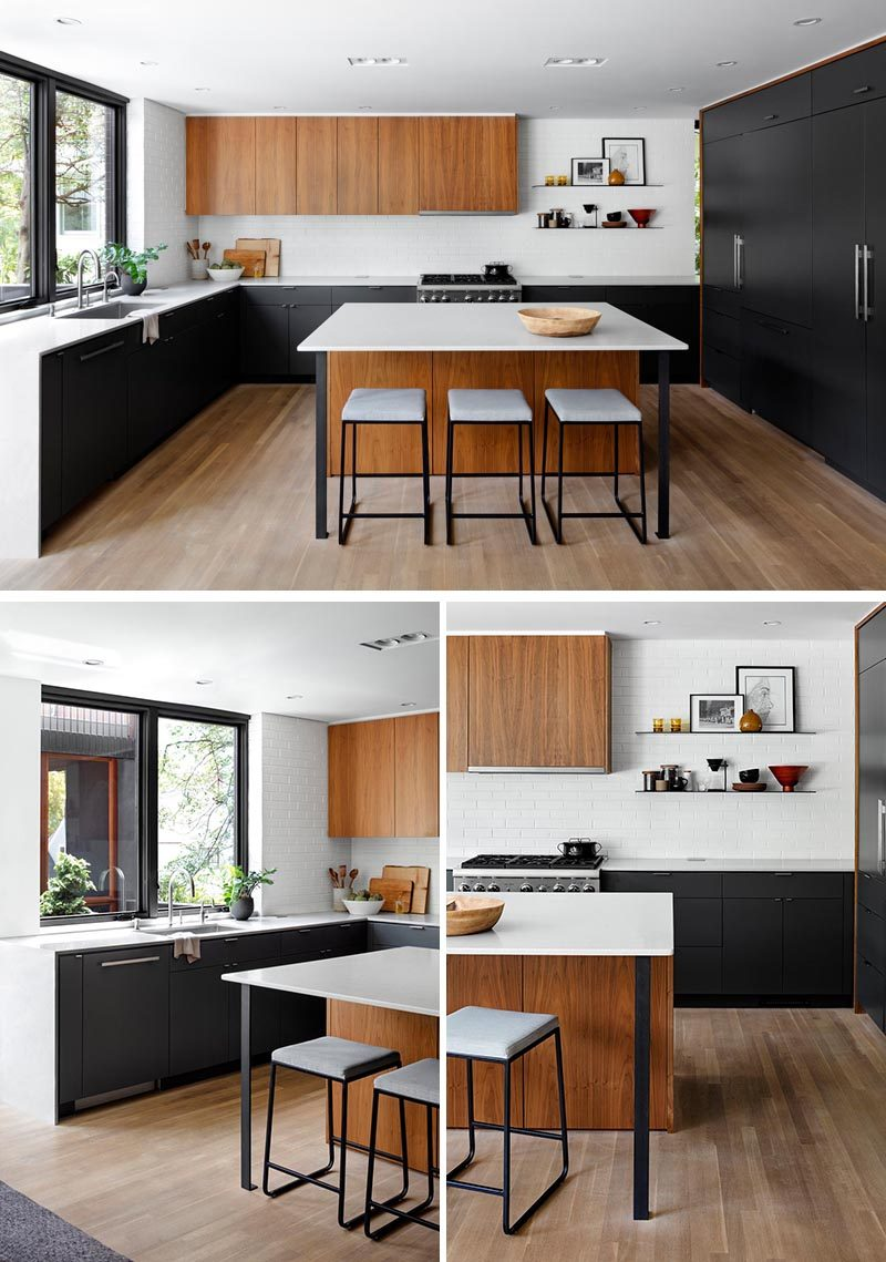 This bright and modern kitchen has black cabinets, with integrated appliances, that are combined with white counters and warm wood cabinetry, while minimalist black shelving provides a place to showcase a variety of objects. #ModernKitchen #BlackCabinets #KitchenDesign