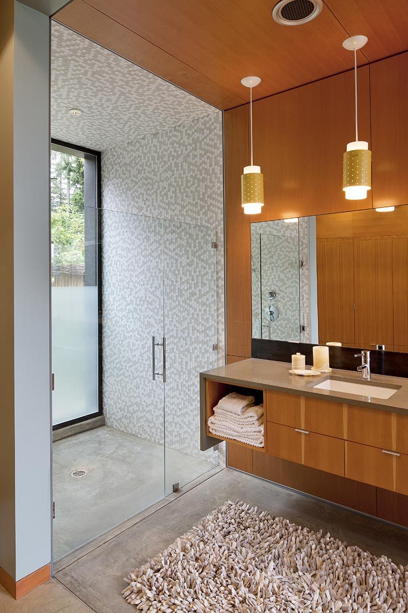 This modern bathroom has a number of design elements that work together to create a calming environment, with clear stained fir plywood adding a natural touch to the space. At one end of the bathroom is the shower, with a white and light grey mosaic tile shower, that even features tiles on the ceiling. #ShowerDesign #ModernShower #ModernBathroom
