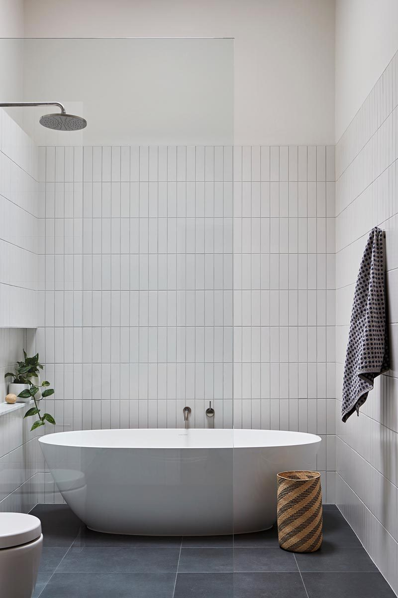 In this modern master bathroom, simple rectangular white tiles have been installed vertically, while Signorino stone tiles cover the floor. The freestanding bathtub shares the space with the shower, and a built-in niche creates a shelf for a plant and bathroom items. #ModernBathroom #BathroomDesign