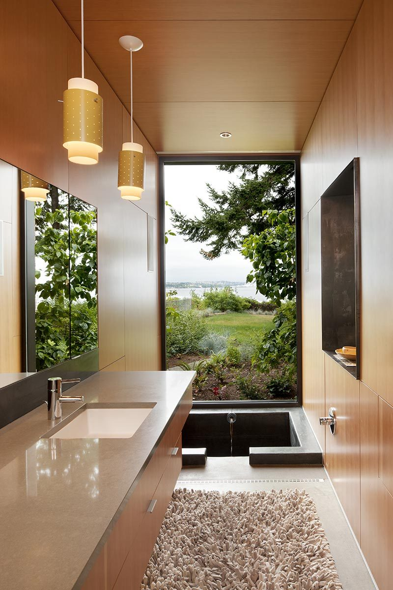 Enjoying the view of this modern bathroom is the 'ofuro' or Japanese style soaking tub. The custom one-of-a-kind bathtub measures in at 3.5' long x 4.5' wide x 4' deep and is made from cast in place concrete. #SunkenBathtub #JapaneseSoakingTub #ModernBathroom #BathroomDesign