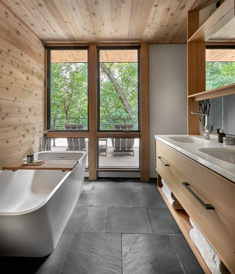 In this modern master bathroom, the freestanding bathtub takes advantage of the windows that overlook a small deck. Opposite the bathtub is a wood vanity with dual sinks, storage drawers, and open shelving. #MasterBathroom #BathroomDesign
