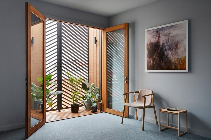 In this modern bedroom with grey walls, wood-framed glass doors open up to a small balcony that hides behind the horizontal slat panels on the facade. #ModernBedroom #GlassDoors #EnclosedBalcony