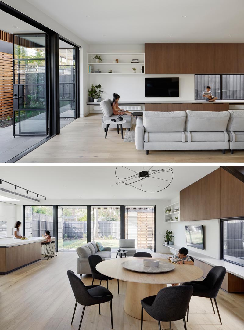 Steel frame glass doors open this modern extension to the backyard, and allow natural light to flood the interior. In the new living room, wood cabinetry and a bench line the wall, while light wood flooring helps to keep the space bright with a sense of warmth. #SteelDoors #GlassDoors #ModernLivingRoom