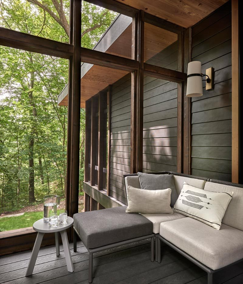 A sunroom off the kitchen of this modern house creates a place to relax in the shade while also enjoying the view of the trees. It also opens to a patio that leads down to the garden. #Sunroom