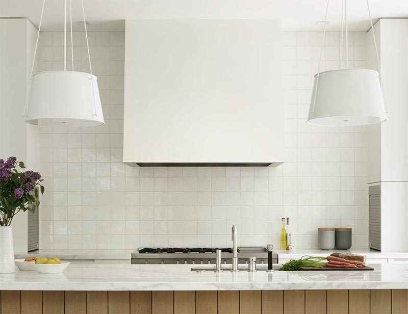 This modern kitchen features two hanging pendant lights, an undermount sink, a white tile backsplash, stainless steel appliances, and a range hood that matches the cabinets. #ModernKitchen #KitchenDesign #WhiteKitchen