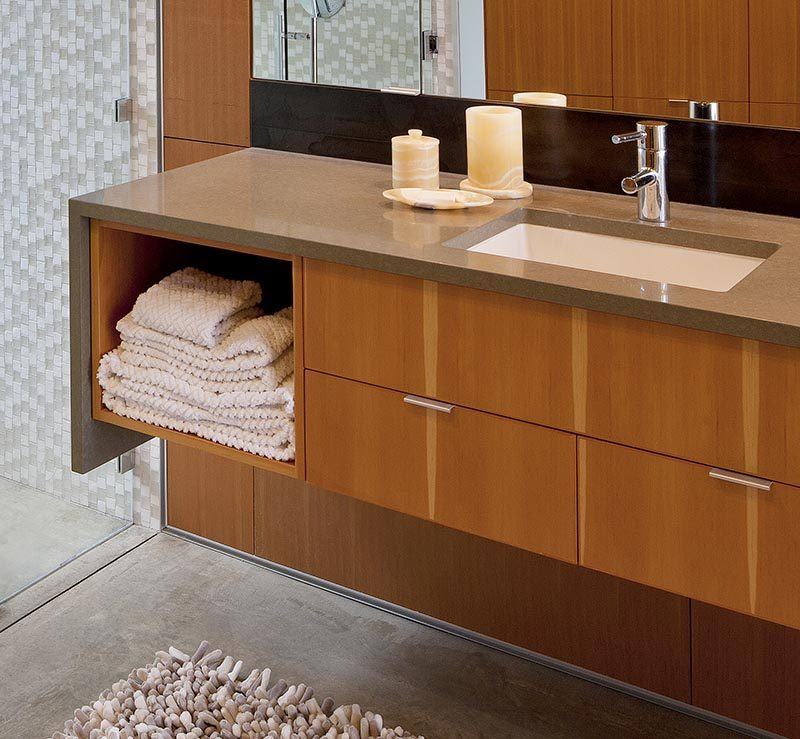 This modern bathroom has a floating wood vanity that features an open shelf and drawers, a waterfall edge counter made from Ceasarstone in mocha with a small fleck pattern, an undermount sink, and a Hansgrohe faucet. #ModernBathtub #FloatingVanity #WoodVanity #Ceasarstone
