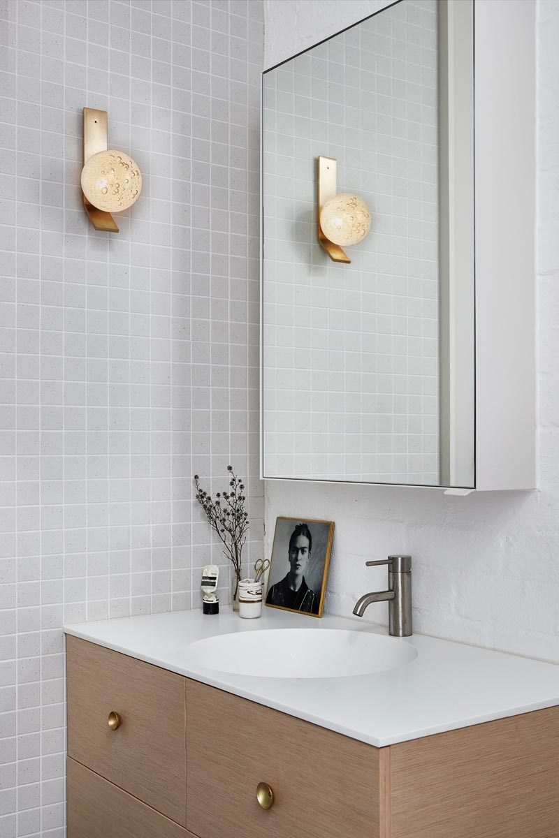 In this modern bathroom, simple grey square tiles cover the wall, while the wood vanity is topped with a white countertop that seamlessly flows into the sink. #ModernBathroom #LightGreyBathroom