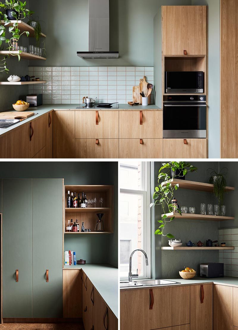 This modern kitchen combines wood cabinets with leather handles, and sage green walls with a white backsplash. #ModernKitchen #GreenWalls #WoodCabinets
