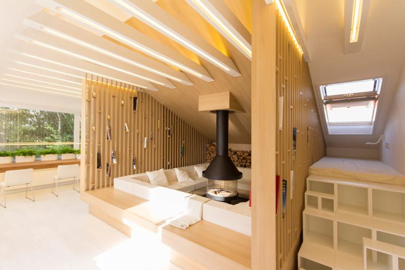 This modern attic has a lounge that wraps around a fireplace, and open wood shelving and ceiling joists with LED lighting. #Lounge #Fireplace #LivingRoom #Shelving #InteriorDesign