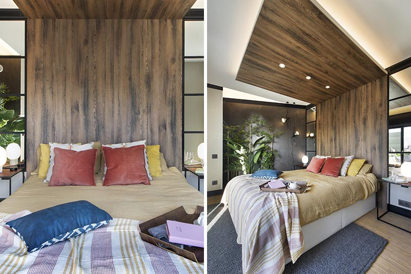 This modern bedroom has a wood headboard that wraps from the wall up onto the ceiling, and acts as an open wood canopy adding a natural touch to the room and defining an area for the bed. It also has hidden lighting that creates a soft glow and highlights the design element. #WoodHeadboard #WrapAroundHeadboard #ModernBedroom #BedroomDesign