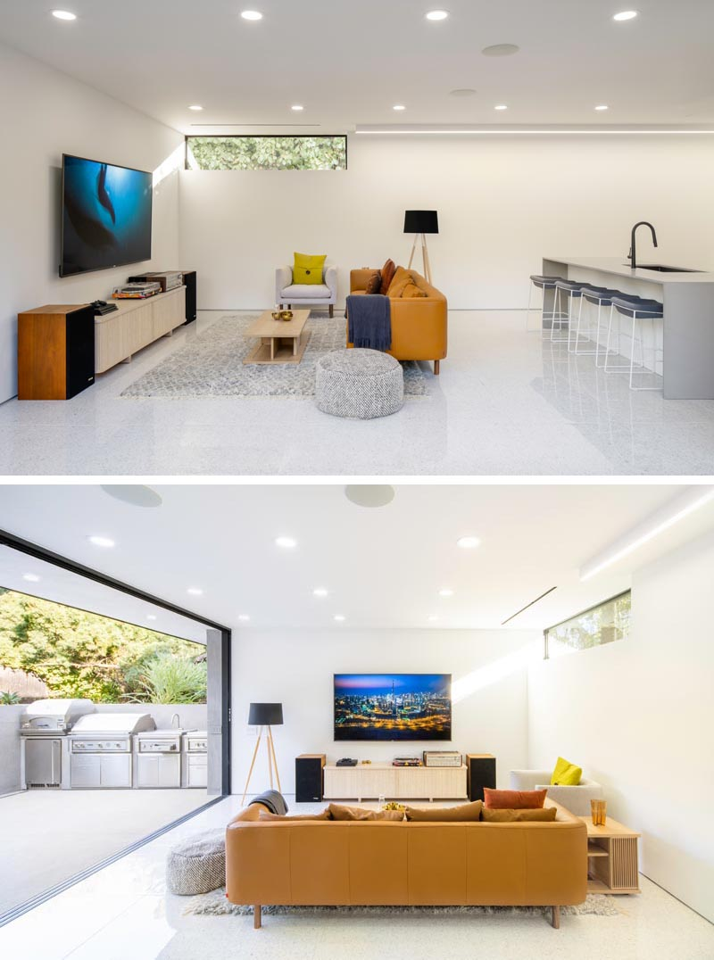 This modern house has a casual open plan living room and kitchen with large sliding glass doors that open to an outdoor bbq area. #Basement #LivingRoom #BBQArea