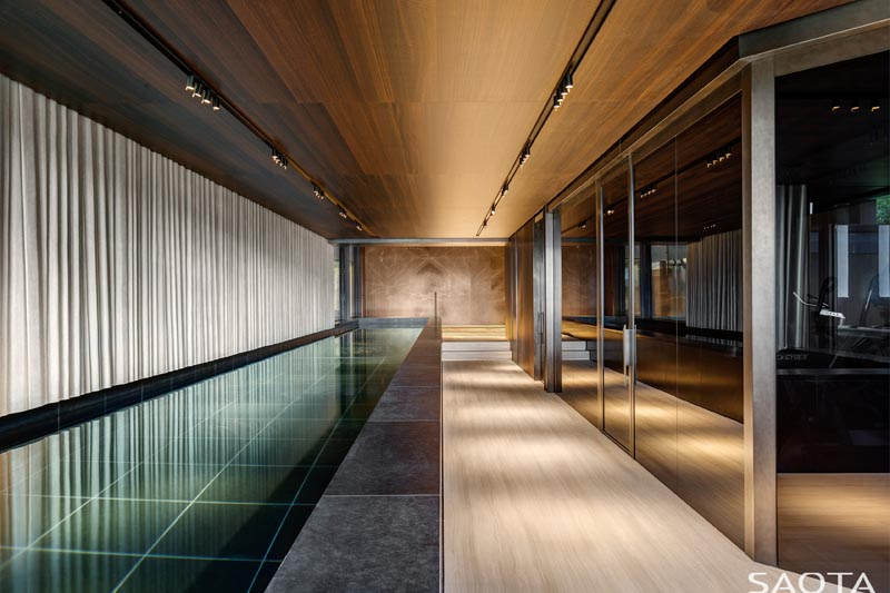 In the basement of this modern house, there's a second pool that's long and narrow, and is positioned beside a wall of windows. #Basement #SwimmingPool