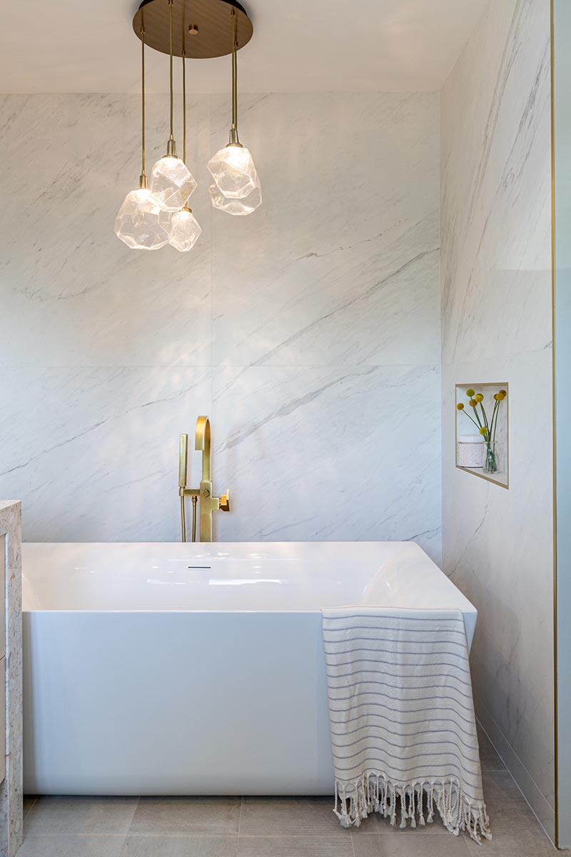 This modern bathroom has a freestanding white bathtub that's recessed into its own alcove. A sculptural multi-light pendant lamps with glass geometric shades, hangs above the bath, highlighting the design. #Bathtub #ModernBathroom