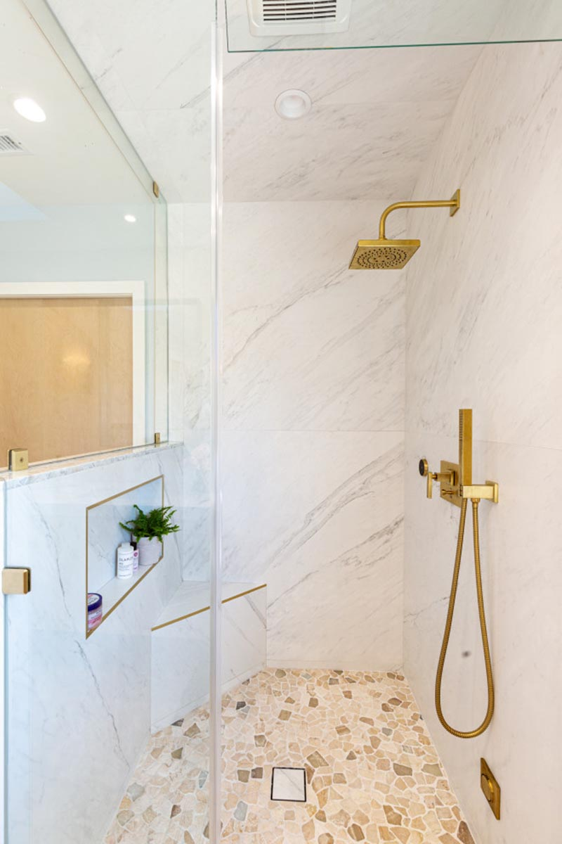 Inside this modern shower, the brass shower head and shower wand contrast the neutral stone, while a shower niche with a brass border provides a place for storage. A small corner bench has also been included in the design of the shower. #ModernShower #GlassShower #EnclosedShower #BrassAccents