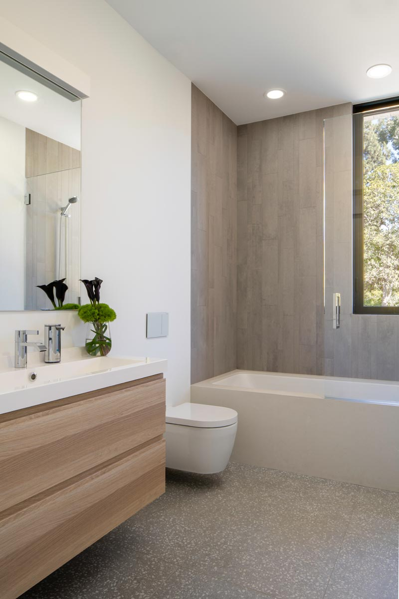 In this modern bathroom, a simple wood vanity has a white countertop, while tiles define the bath and shower. #BathroomDesign #ModernBathroom