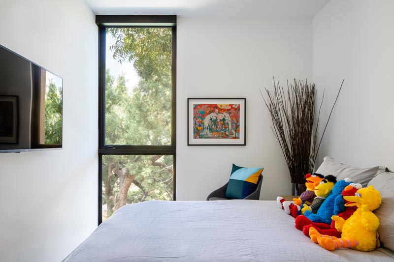 In this modern bedoom, colorful accents brighten up the mostly white interior. #ModernBedroom #BedroomDesign