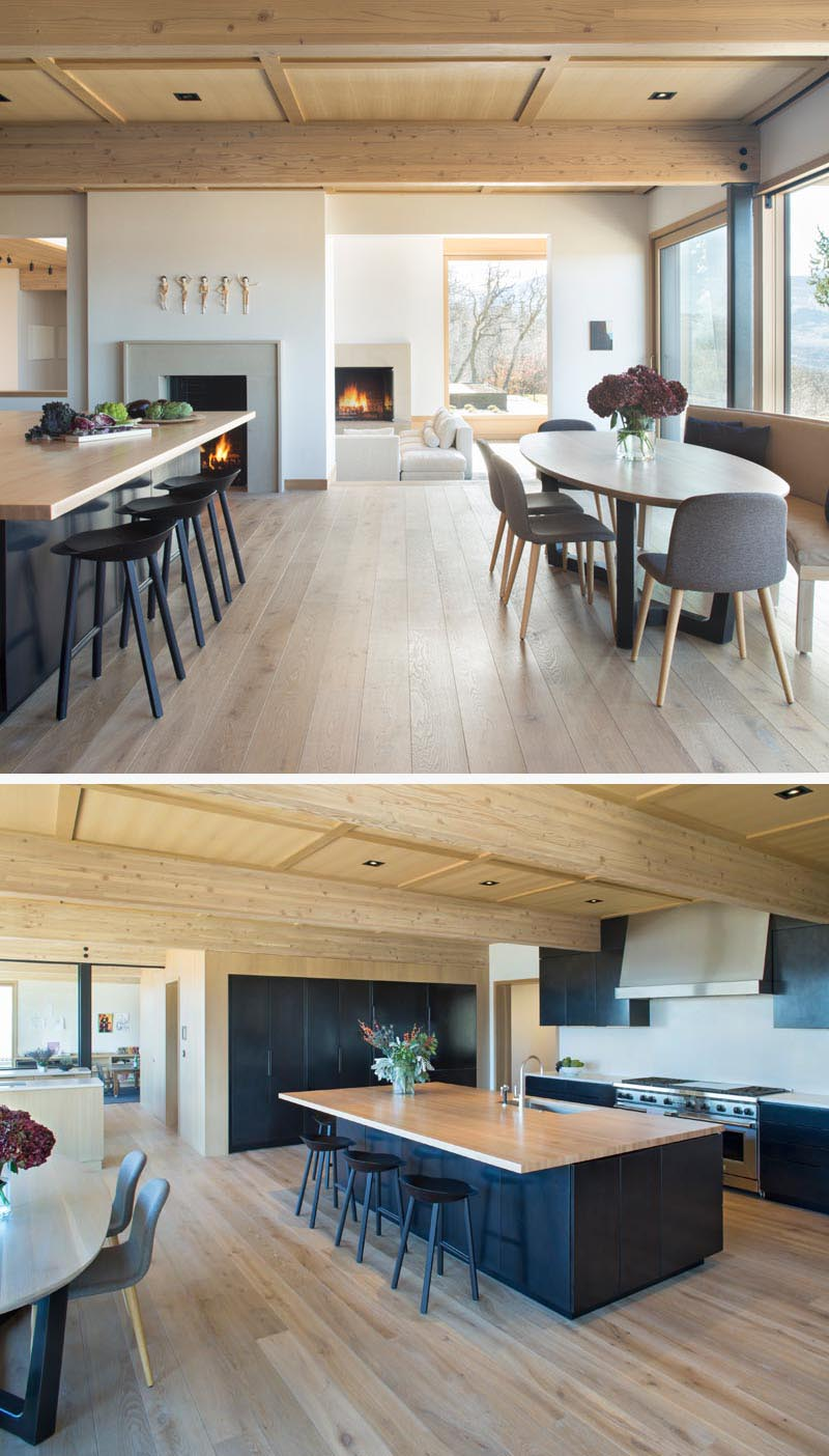 In this modern open plan breakfast nook and kitchen, there's a fireplace and minimalist black cabinets that have been combined wood details, like the large wood island countertop. #ModernKitchen #Fireplace #BlackKitchenCabinets